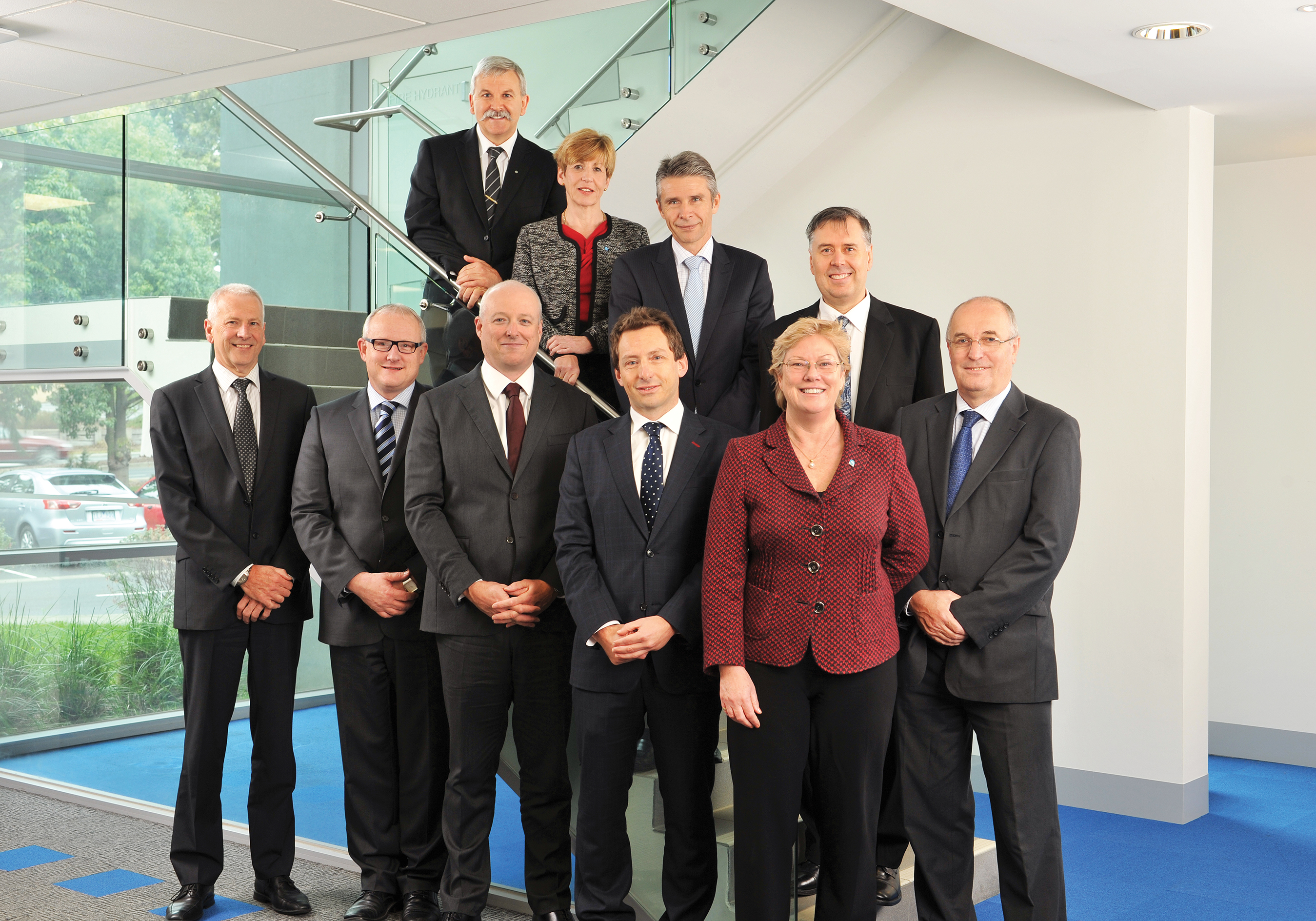 Executive team 2012- 13. From left to right, back row on stairs to front row: Dr Tom Hatton PSM, Ms Hazel Bennett, Mr Mike Whelan, Mr Craig Roy, Dr Alastair Robertson, Dr Calum Drummond, Dr Andrew Johnson, Mr Rod Bloom, Dr Megan Clark (Chief Executive), Dr David Williams.