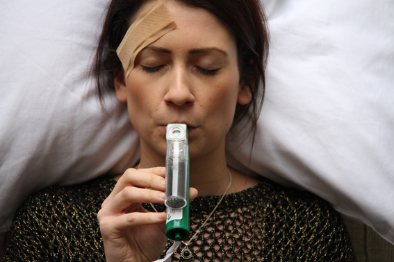 Lady administering pain relief through a device known as the 'Green Whistle'.