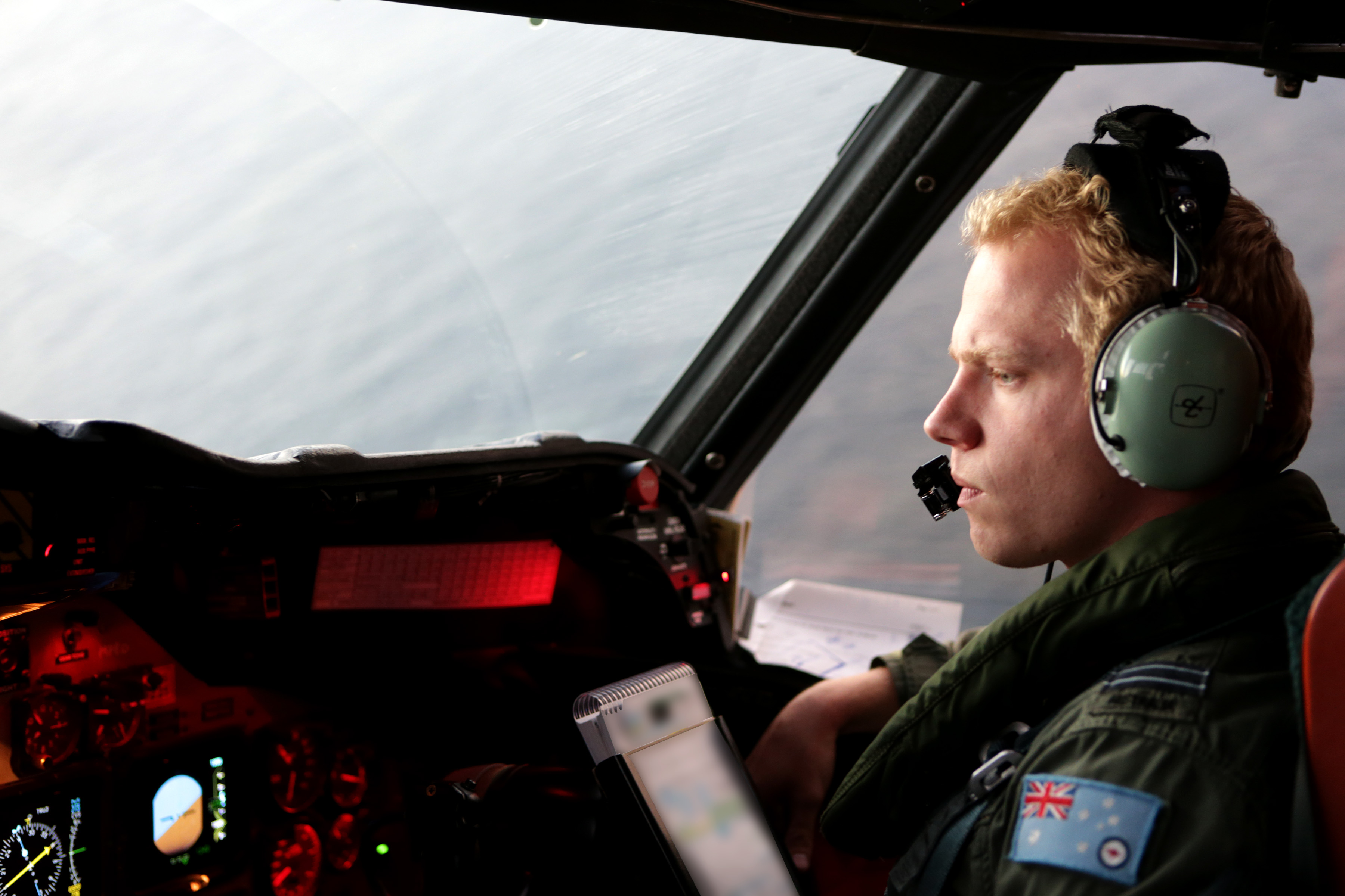 A man in the cockpit of a plane flying over the ocean.