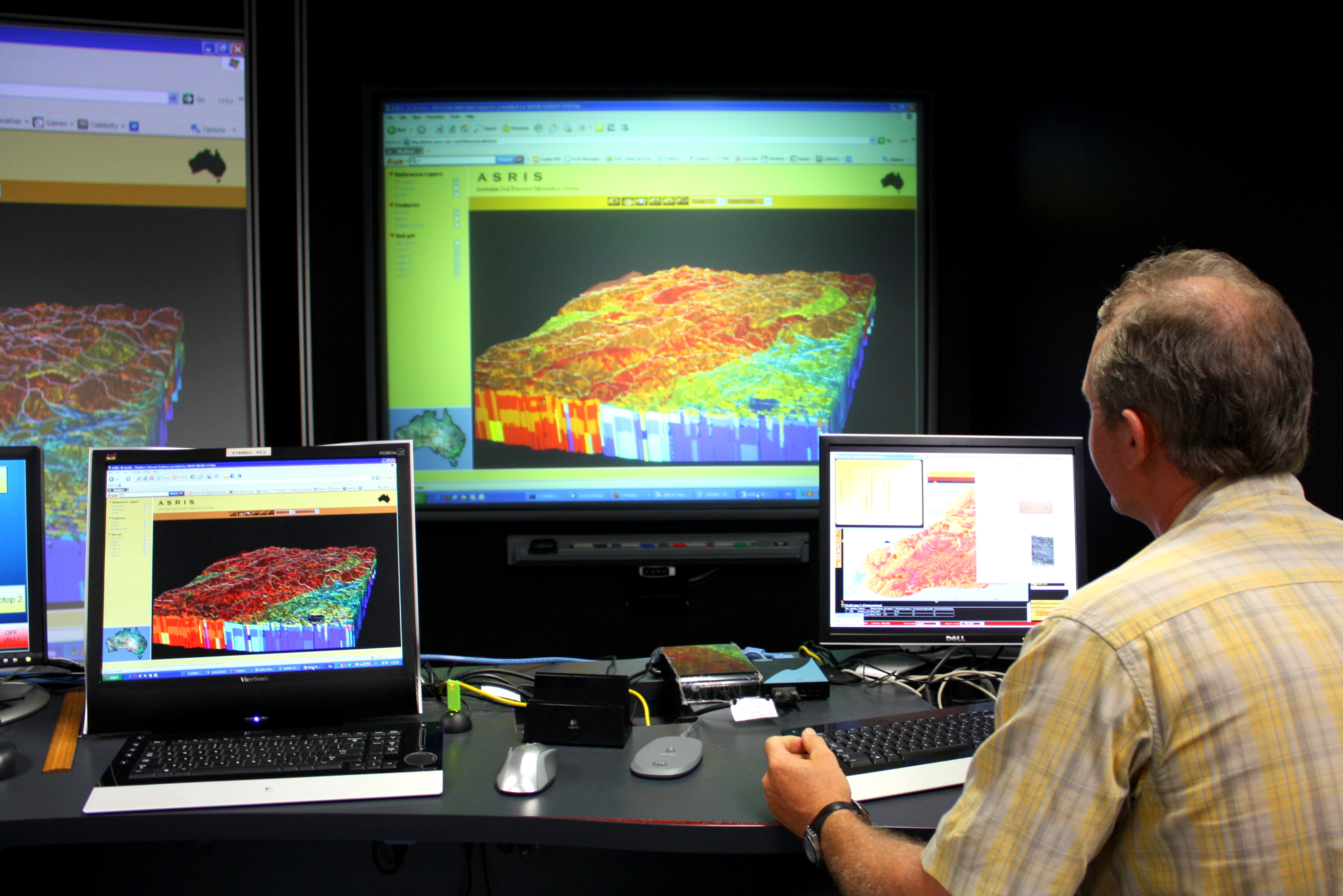 Scientist sitting in front of a several computer screens using the Soil and Landscape Grid of Australia database.