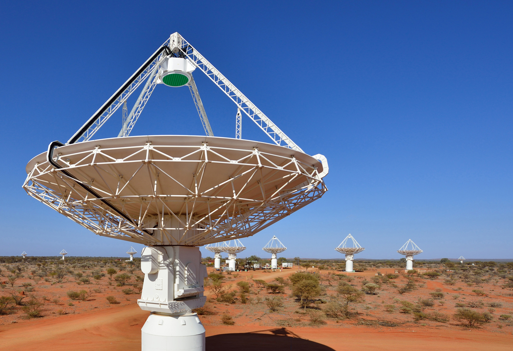 Close up of one of the ASKAP telescopes, with several others in the background.