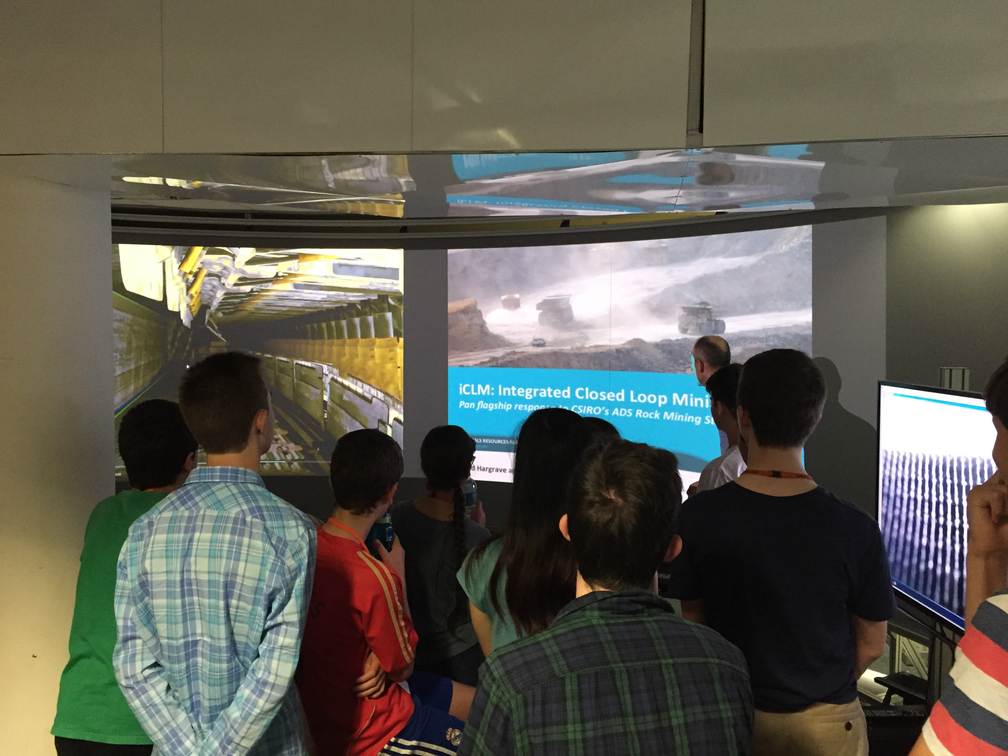 Students standing around several large screens as part of an immersive visualisation facility.