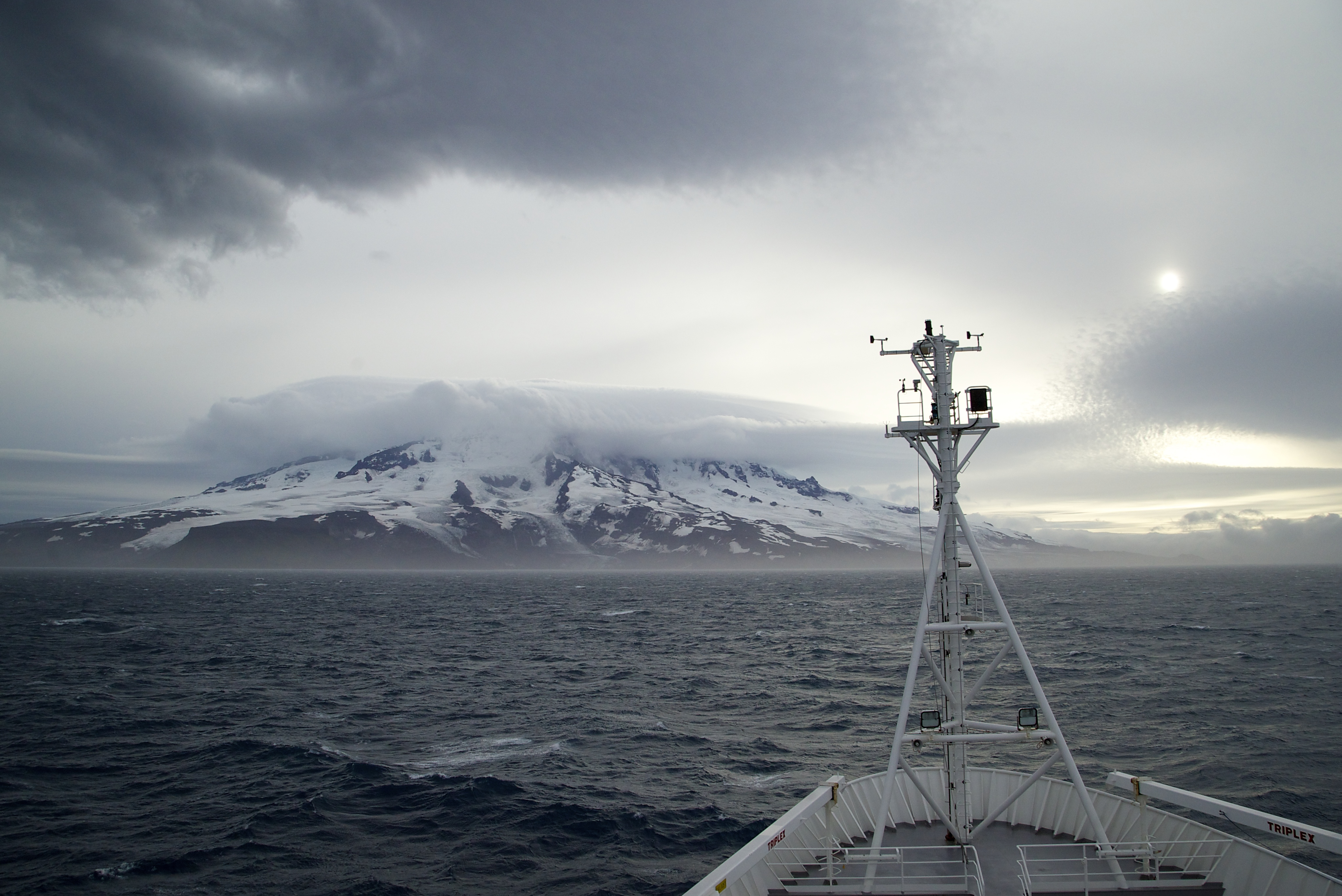 View across the bow of the RV Investigator while at sea heading towards a snow covered Heard Island.