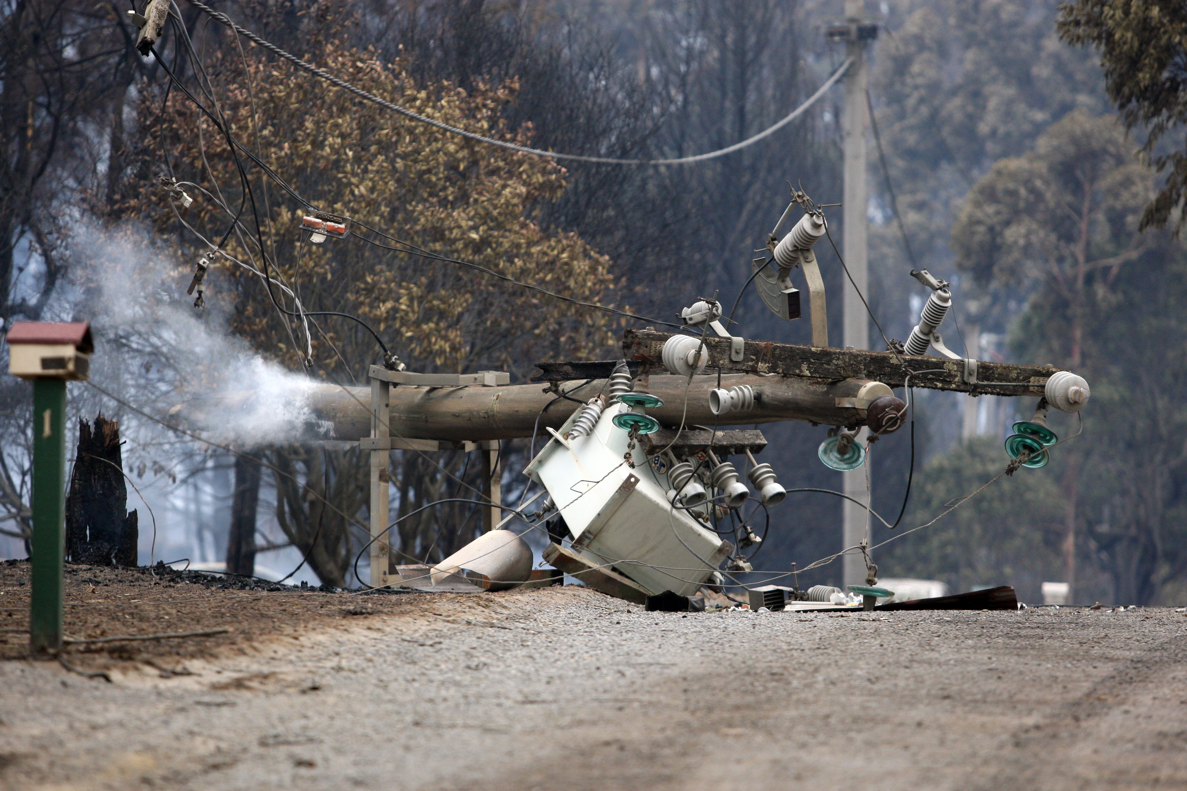Power pole with transformer collapsed across a road following a bushfire.