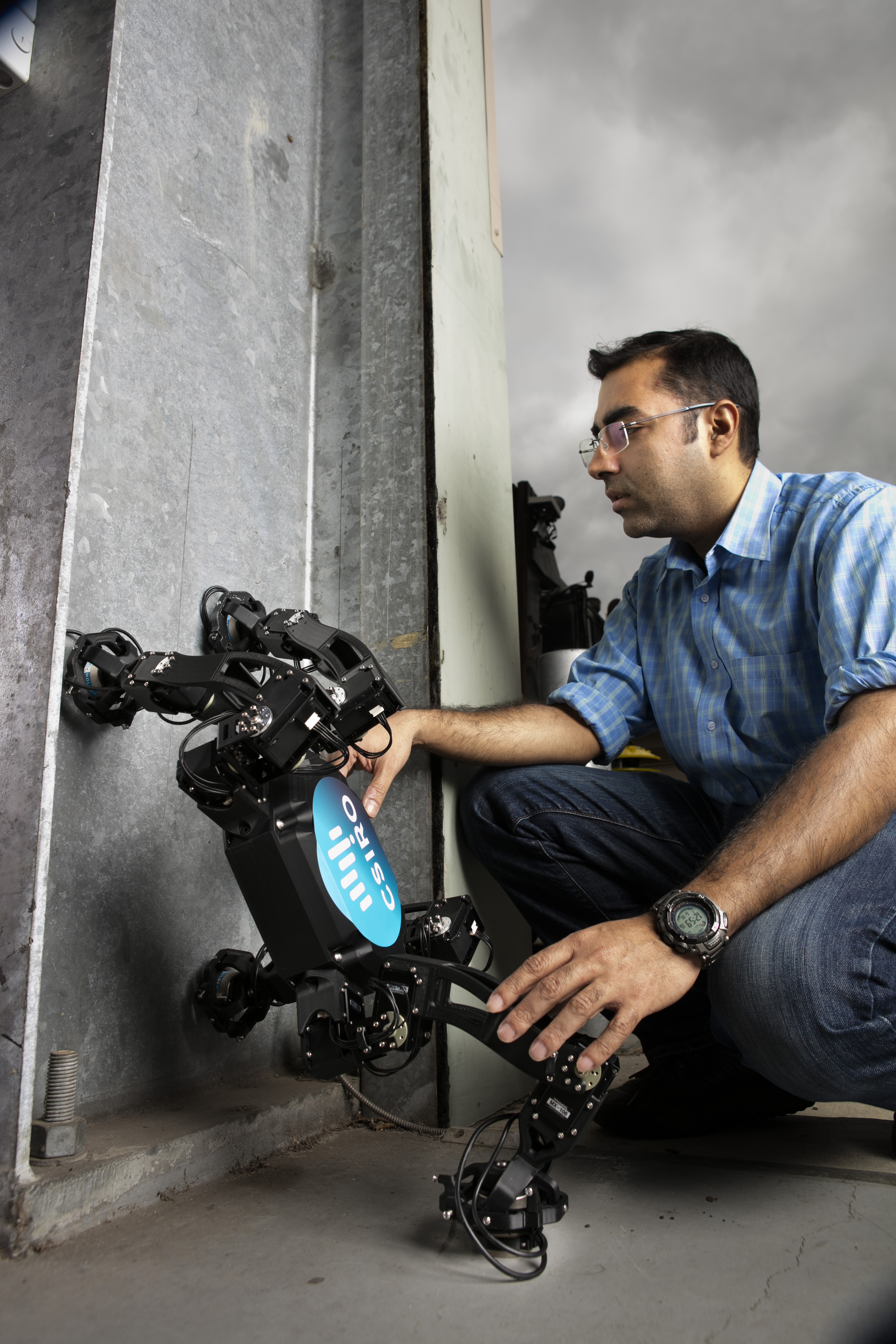 Scientist testing a legged-robot equipped with controllable magnetic adhesion as it begins to walk up a vertical surface.