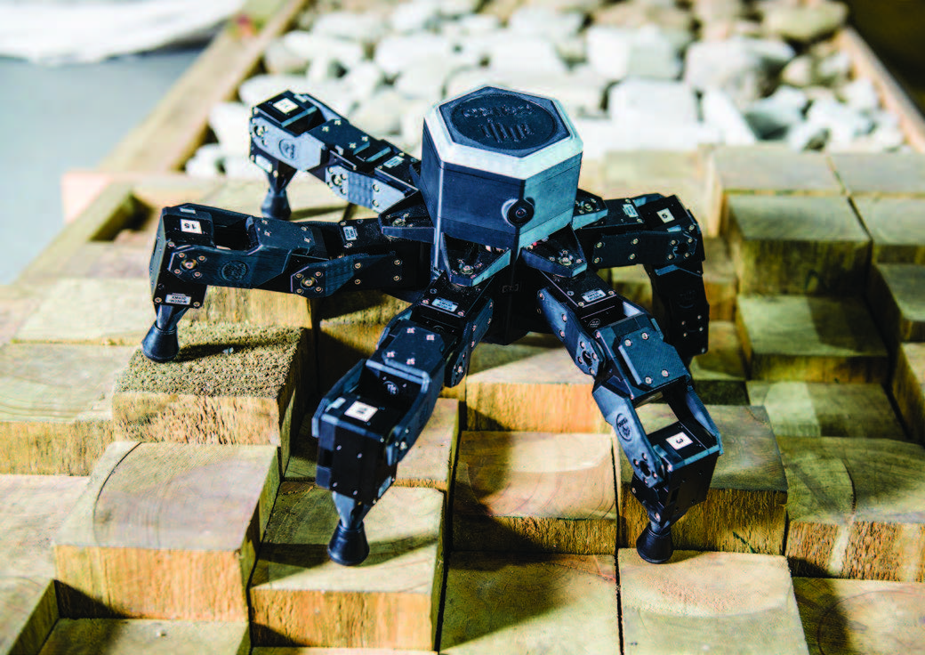 an image of a black csiro robot sitting on square wooden blocks