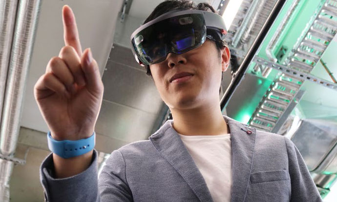 person wearing black virtual reality goggles and pointing their right pointer finger into the air. The person is in a factory with metal pipes on the roof. They are wearing a pale tshirt with a grey jacket and blue wristband