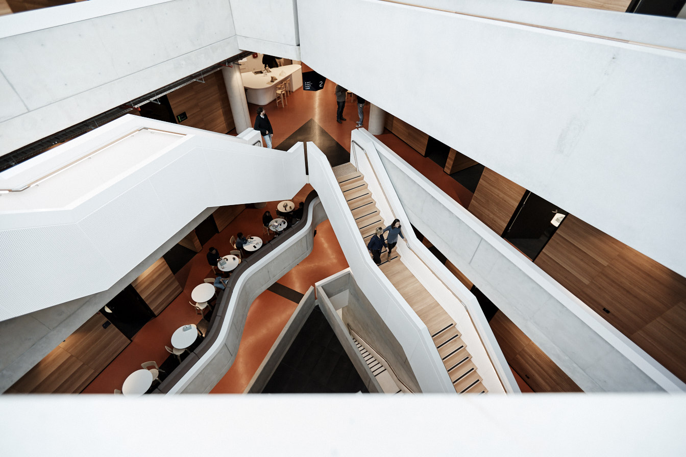 Two people working down Synergy Building main staircase.