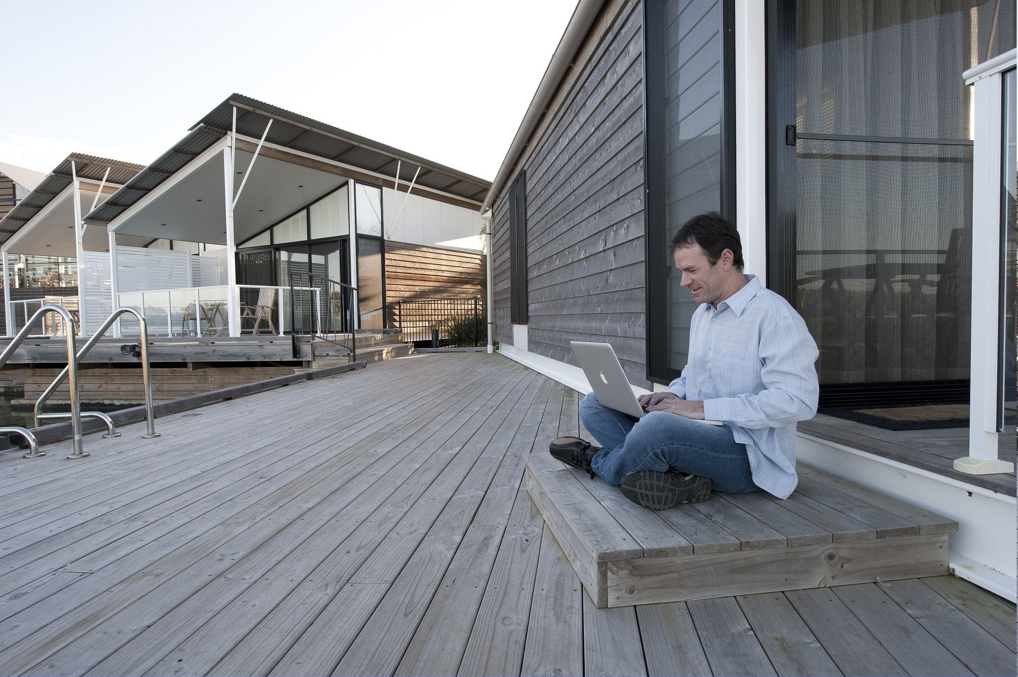 Man sitting on timber verandah with laptop computer on lap.