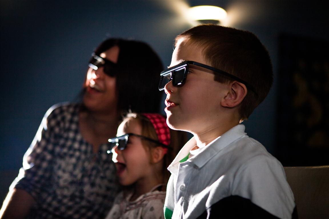 A woman and two children wearing dark glasses