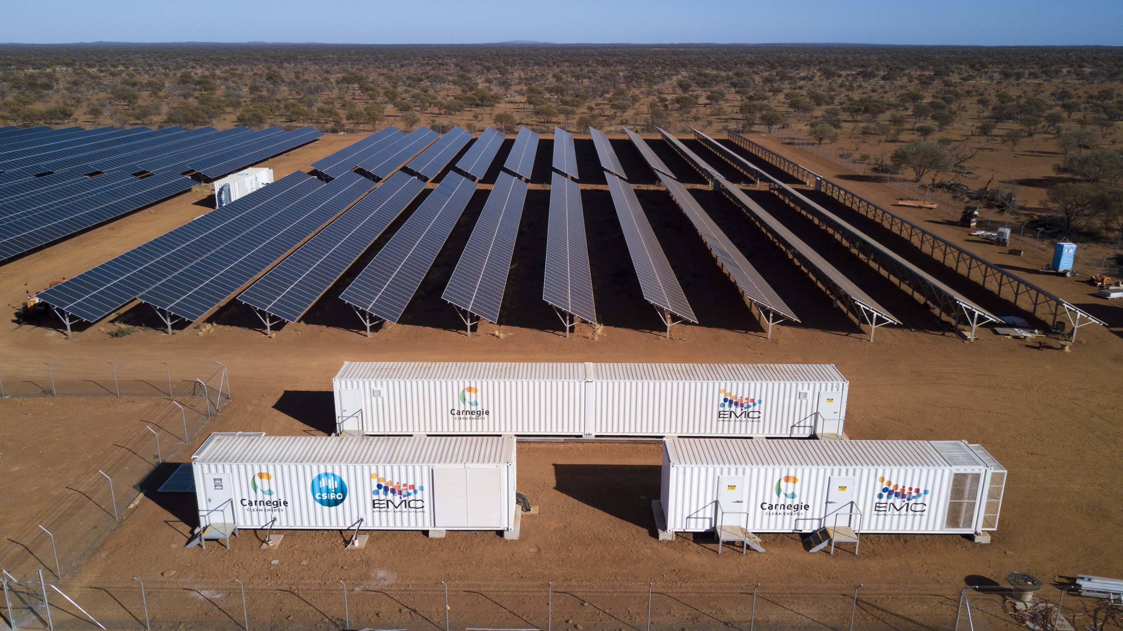 Containers in foreground with rows of photovoltaic cells behind, situated in red desert surroundings