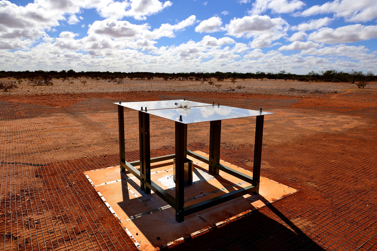 Small Rectangular metal radio telescope sitting on block of concrete surrounded by red dirt