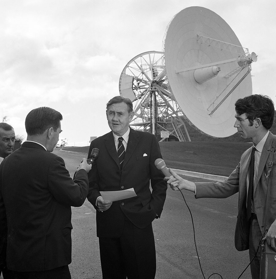 A black and white photograph of a man in a suit facing the camera, he's holding a piece of paper; three other men are holding mircophones and facing towards their interviewee; a large antenna dish is in the background.