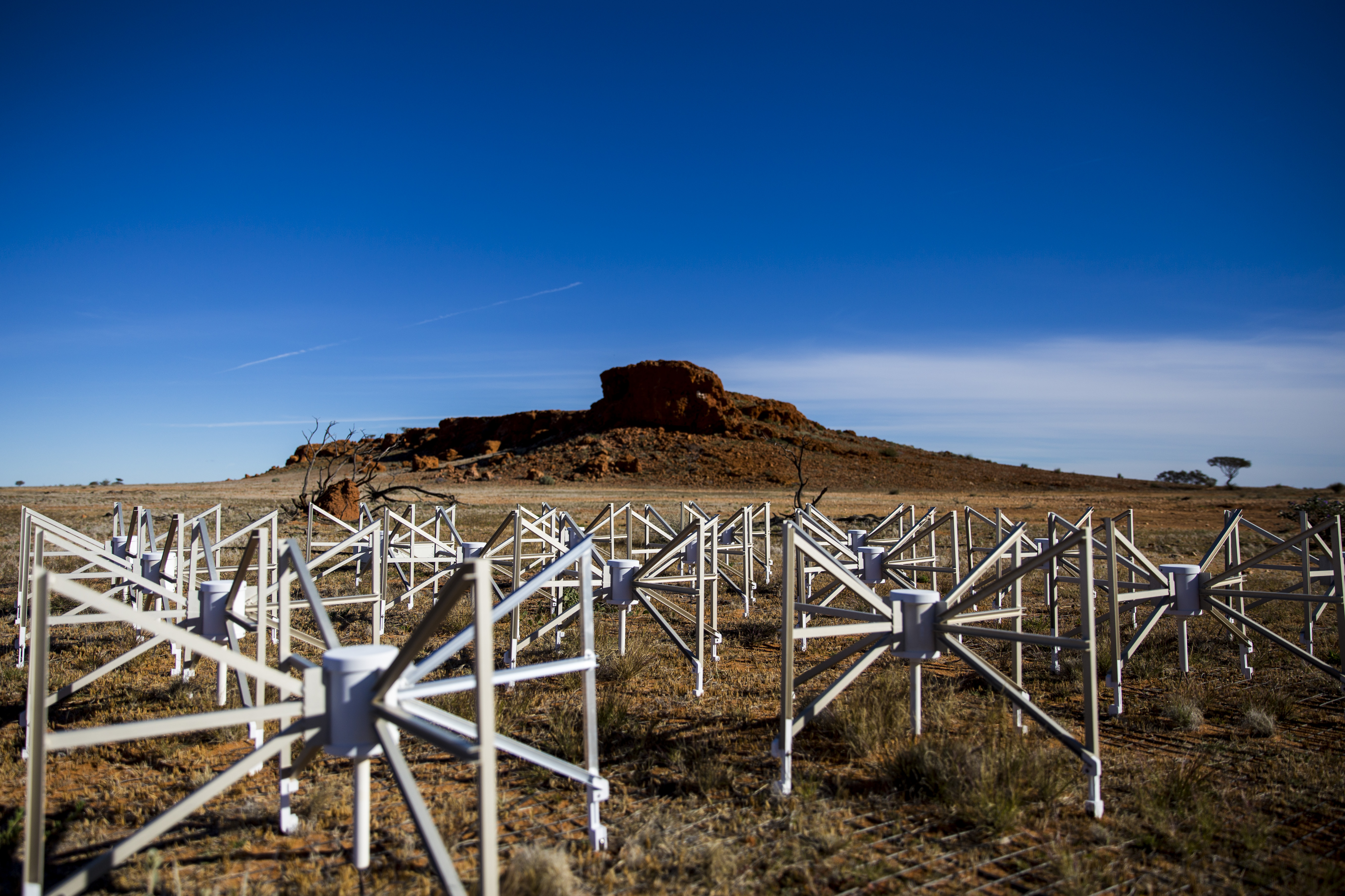 Group of short metal spider-like antennas in foreground with small red hill and blue sky in background