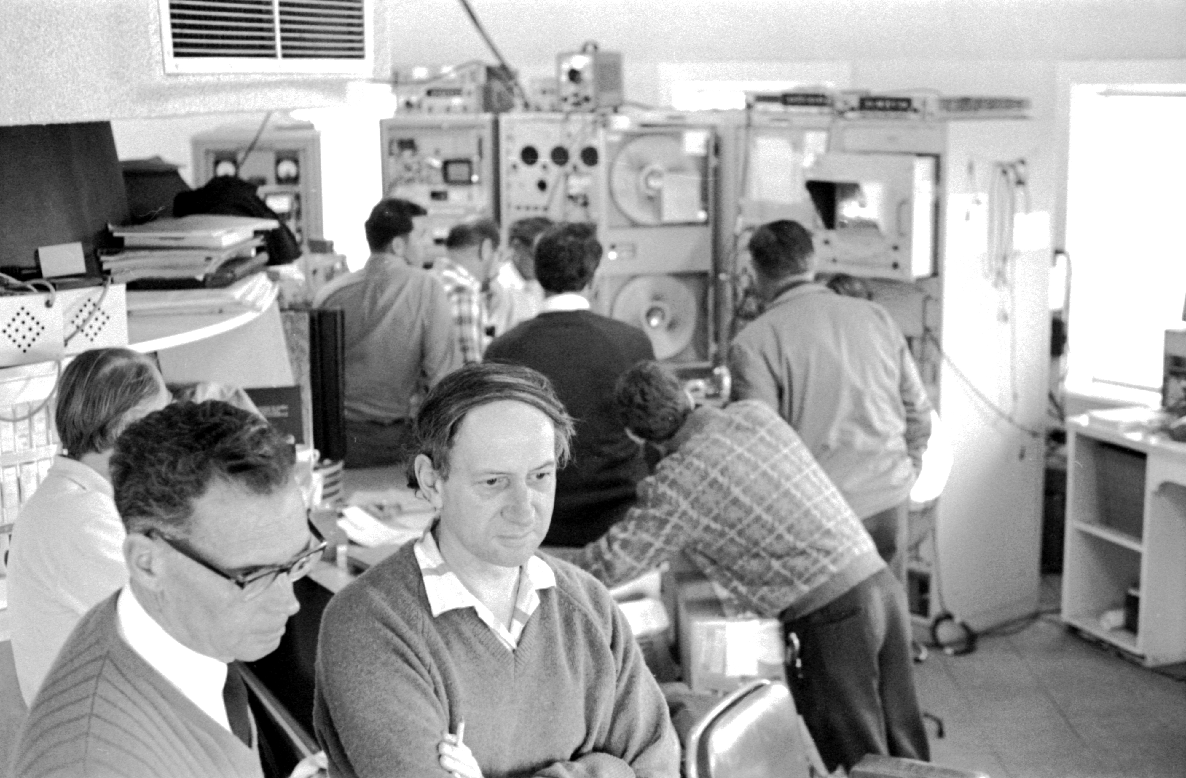 A black and white photograph of two men in the foreground looking at something to the side of the camera; in the background six men with their backs to the camera are looking at a bank of controls and switches.