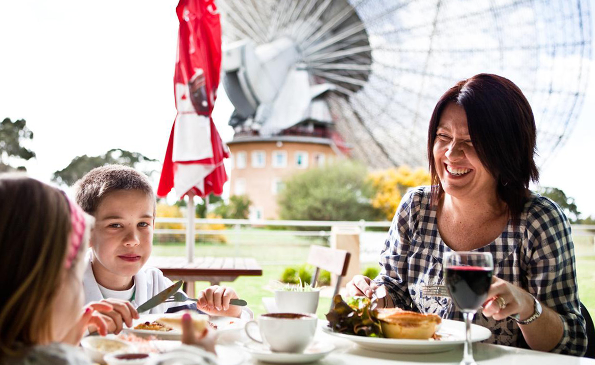 A woman and two children sitting at a table eating with a large telescope dish in the background.