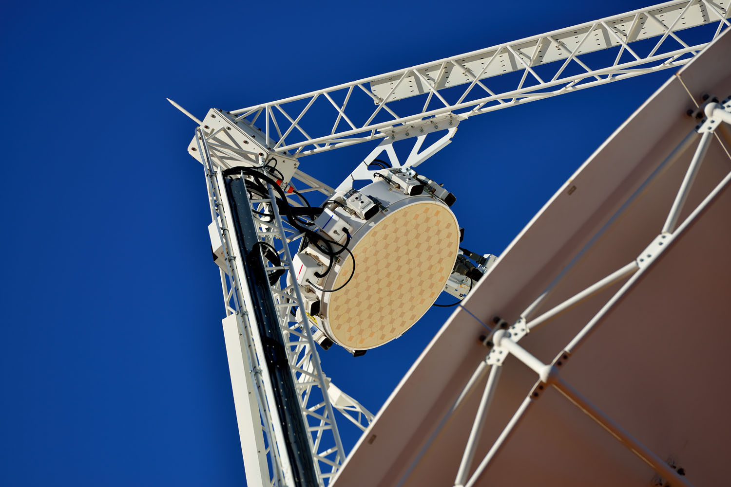 White circular object attached to the apex of a radio telescope antenna
