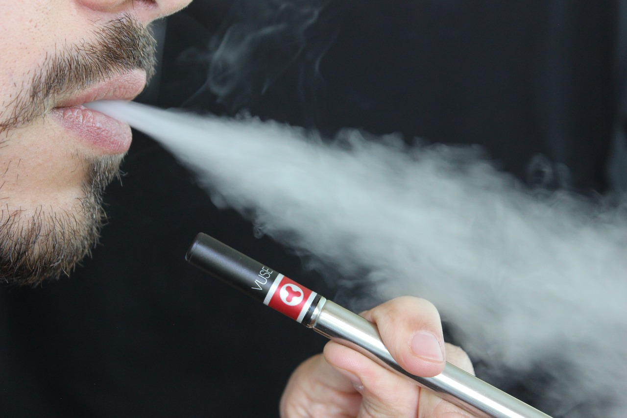 close-up image of a man blowing smoke from an e-cigarette