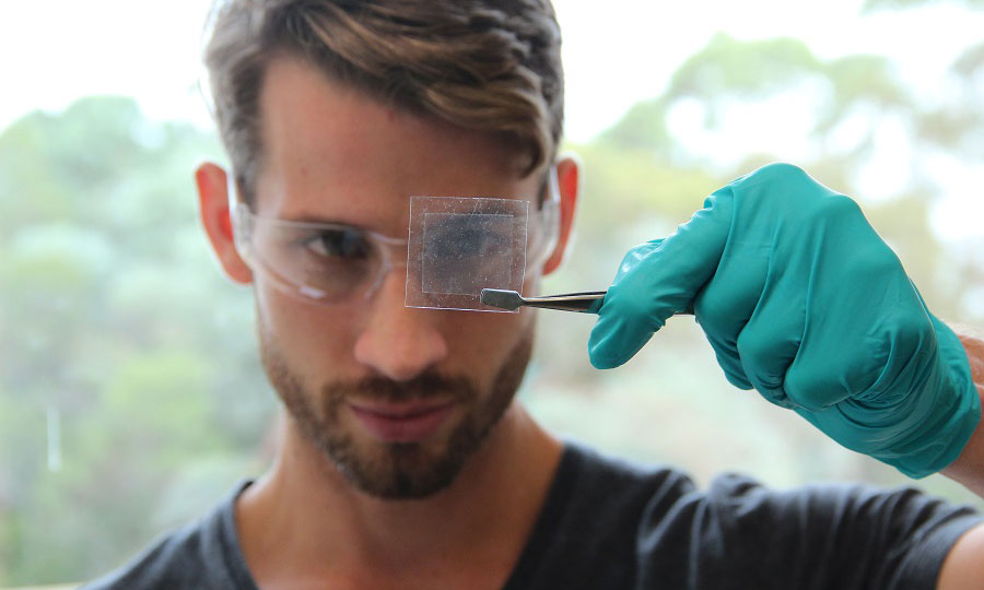 A scientist holding up some graphene with tweezers
