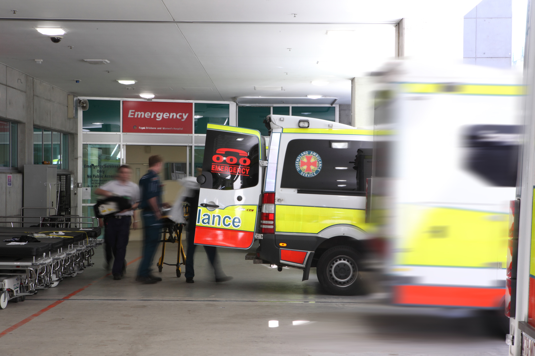 The side of an ambulance, painted white, yellow and red, with the back door open; paramedics are taking a patient on a trolley from the vehicle to the entrance of the emergency departmentatient on