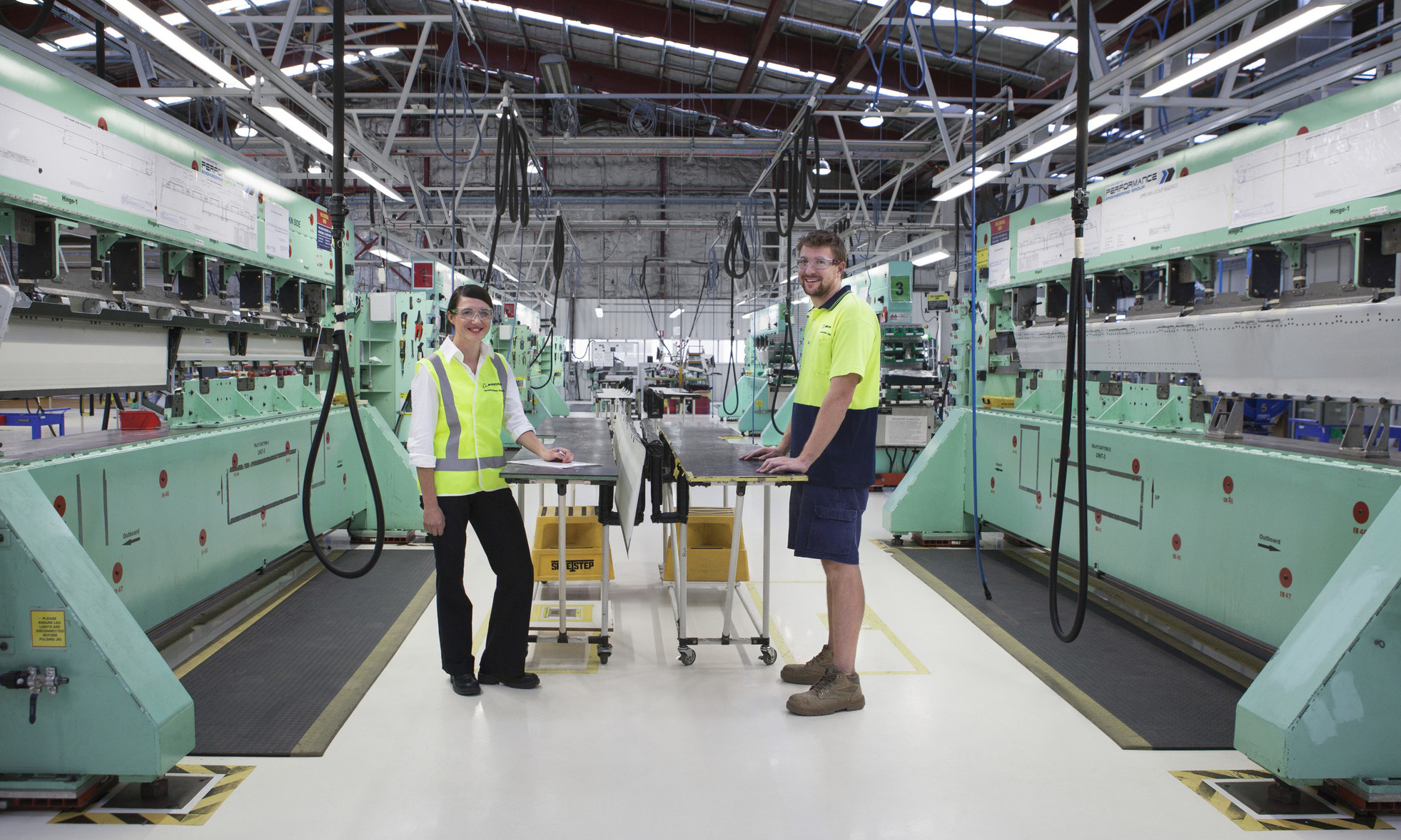 Two peopole in fluro vests standing in a factory.