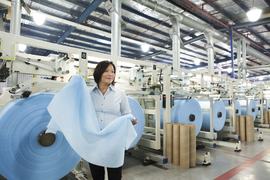 CSIRO staff member in factory at Textor Technologies production facility with moisture-trapping fabric co-developed with CSIRO. Rolls of fabric in background.