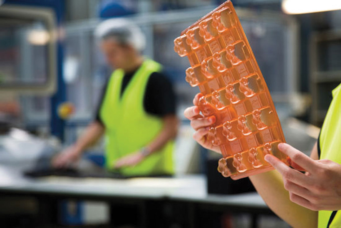 A researcher holding up a plastic tray in a factory