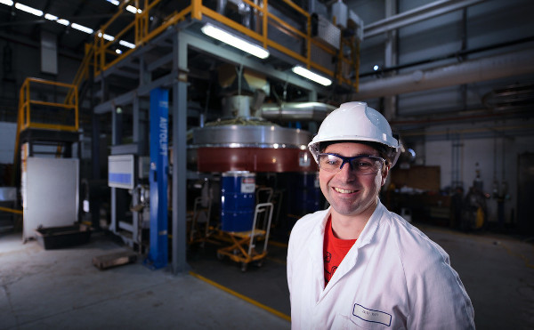 Male researcher, Jason Donnelly, wearing helmet, safety glasses and white lab coat, standing in front of Dry slag granulation rig.