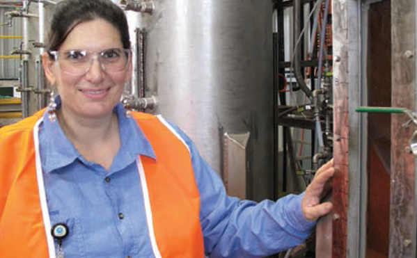 A lady in a bright orange safety jacket standing in front of a large steel cylinder.