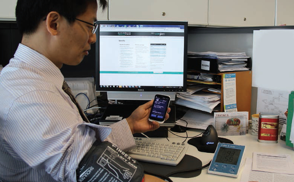 Dr Ding using a mobile application to log his blood pressure reading