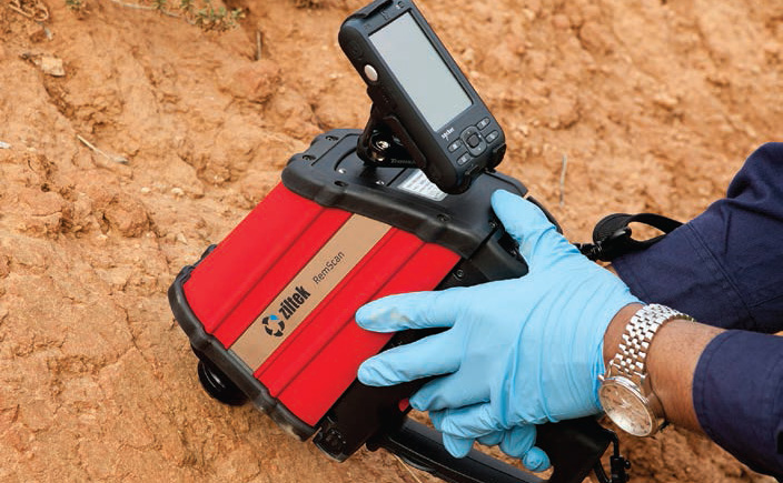 A person wearing blue gloves holding a red device with a screen on top over the ground.
