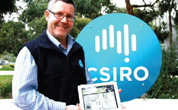 A man standing in front of a CSIRO logo holding a ipad with chemical structures on the screen.