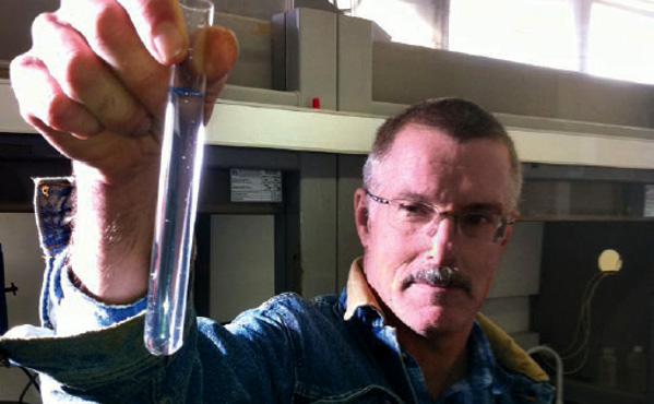 A man holding up a test tube