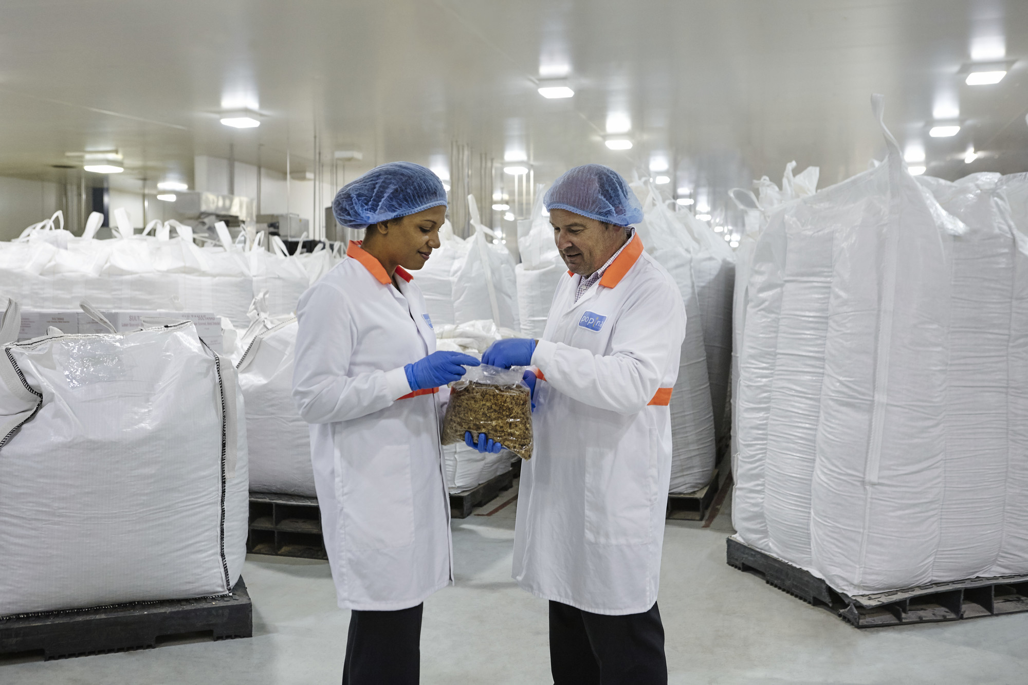 two people in lab coats and hair nets in a factory