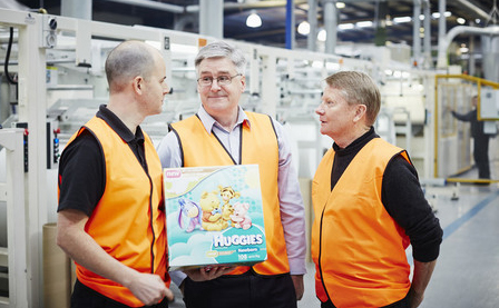 Three men in orange vests in a factory one is holding a box of Huggie's nappies