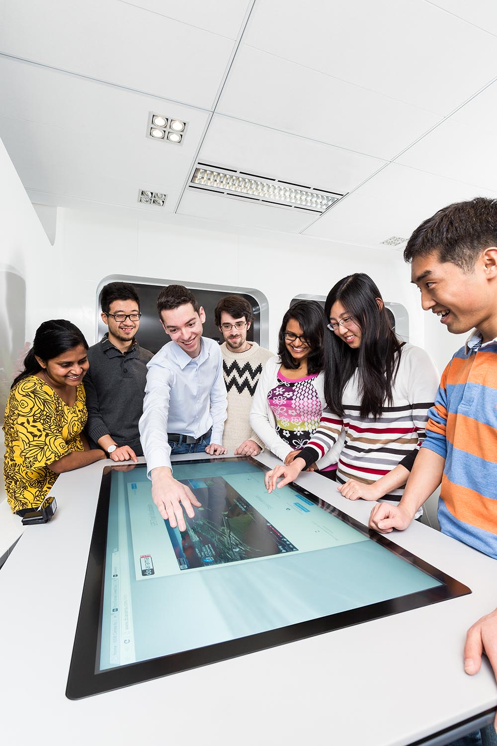 A group of men and women are standing around a desk that has a screen built into it, one man is reaching outo to touch the screen