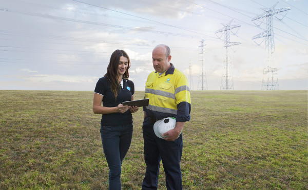 Female and male researchers examining iPad in grass field with powerlines in background.