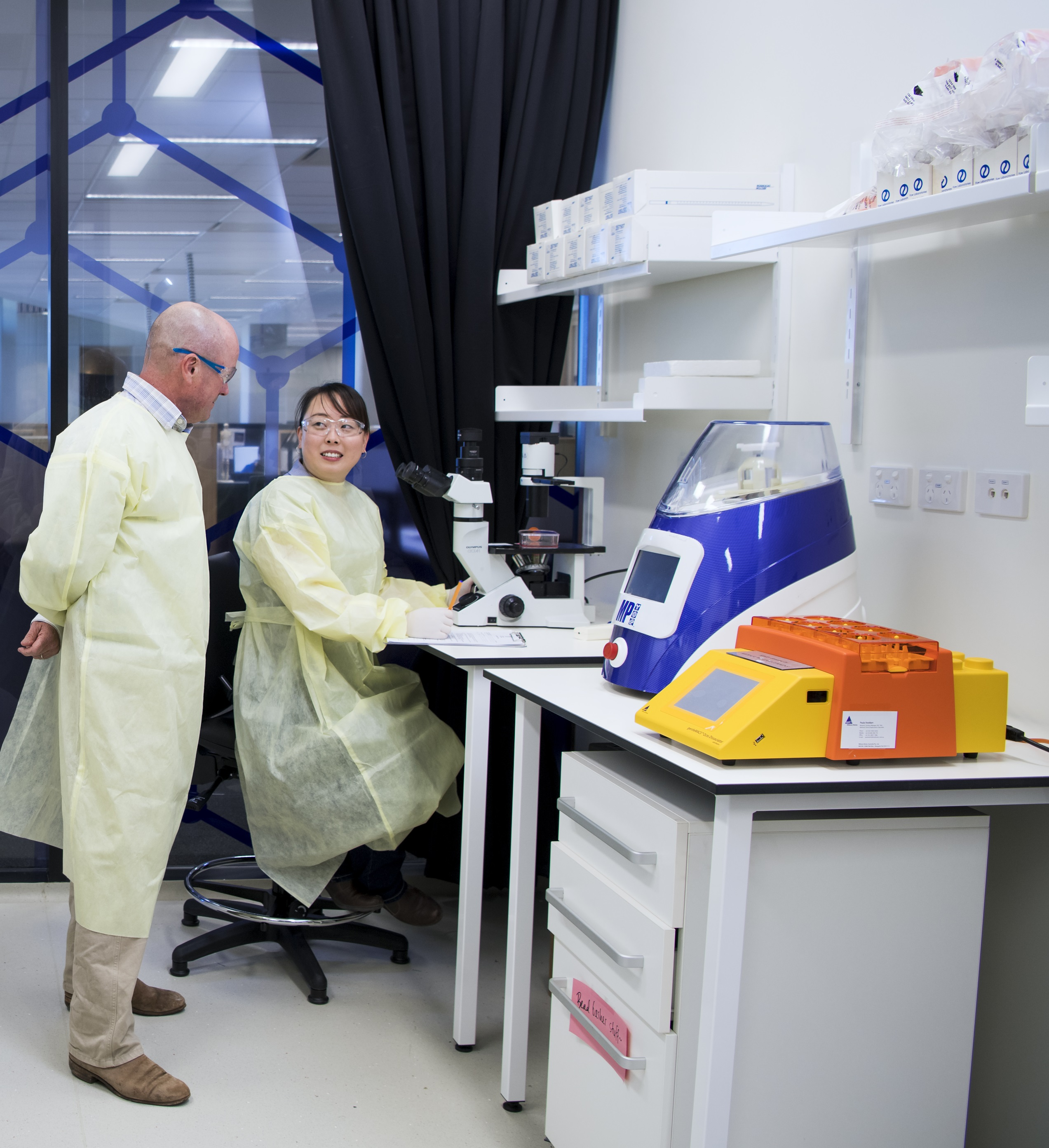 A male and female scientist wearing disposable lab coats work at a bench in a brightly lit lab with brightly coloured equipment around them.