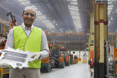 A man in a fluro vest holding a car part in a factory