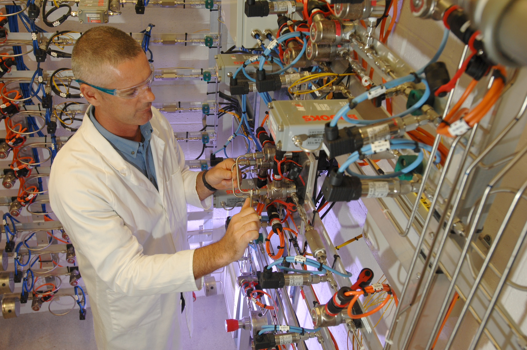 A male scientist in lab coat and safety glasses standing among racks of components