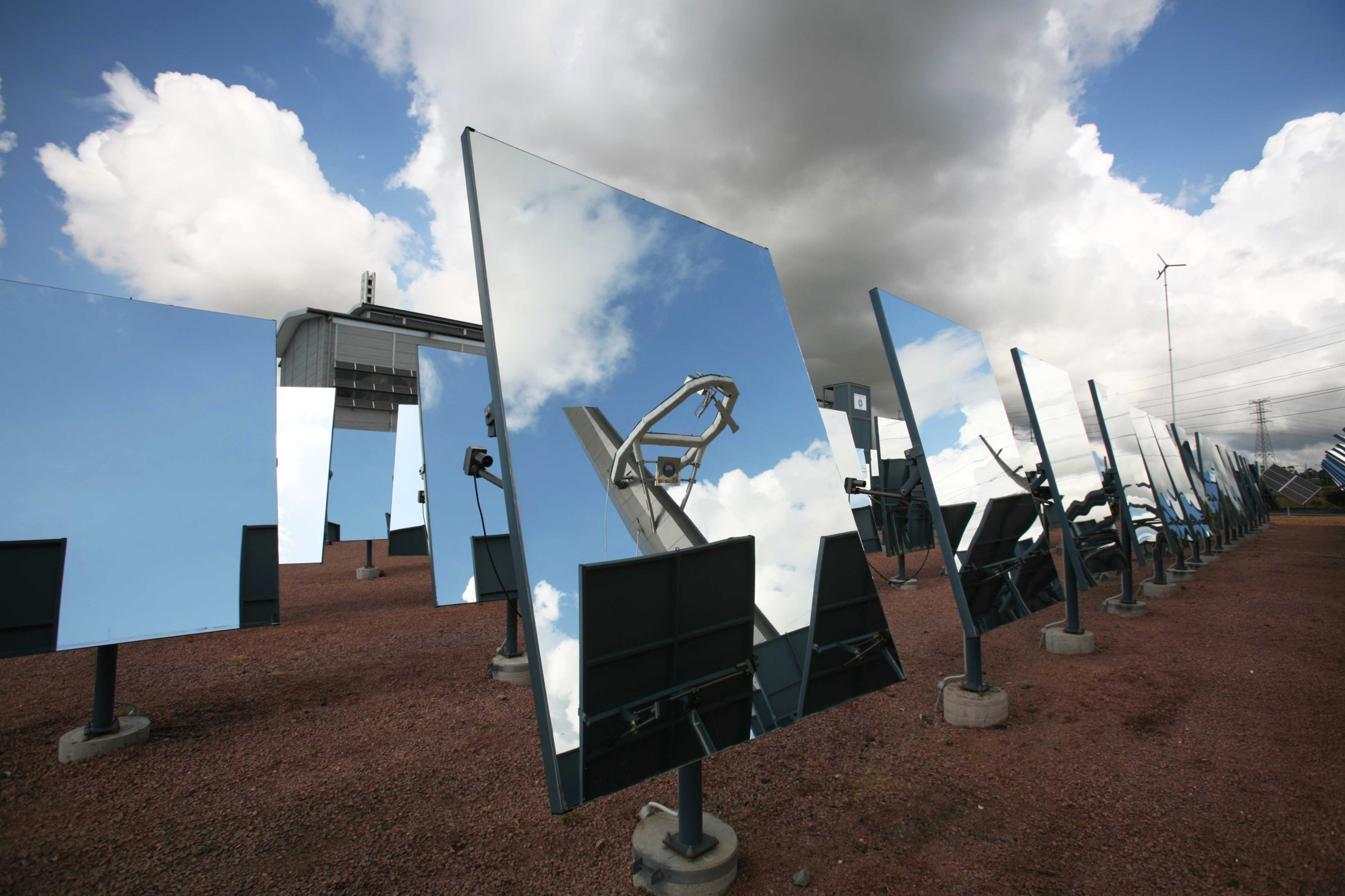 Rows of mirrors at a heliostat mirror field under a blue sky with small clouds. Reflected in one mirror is the collector tower.