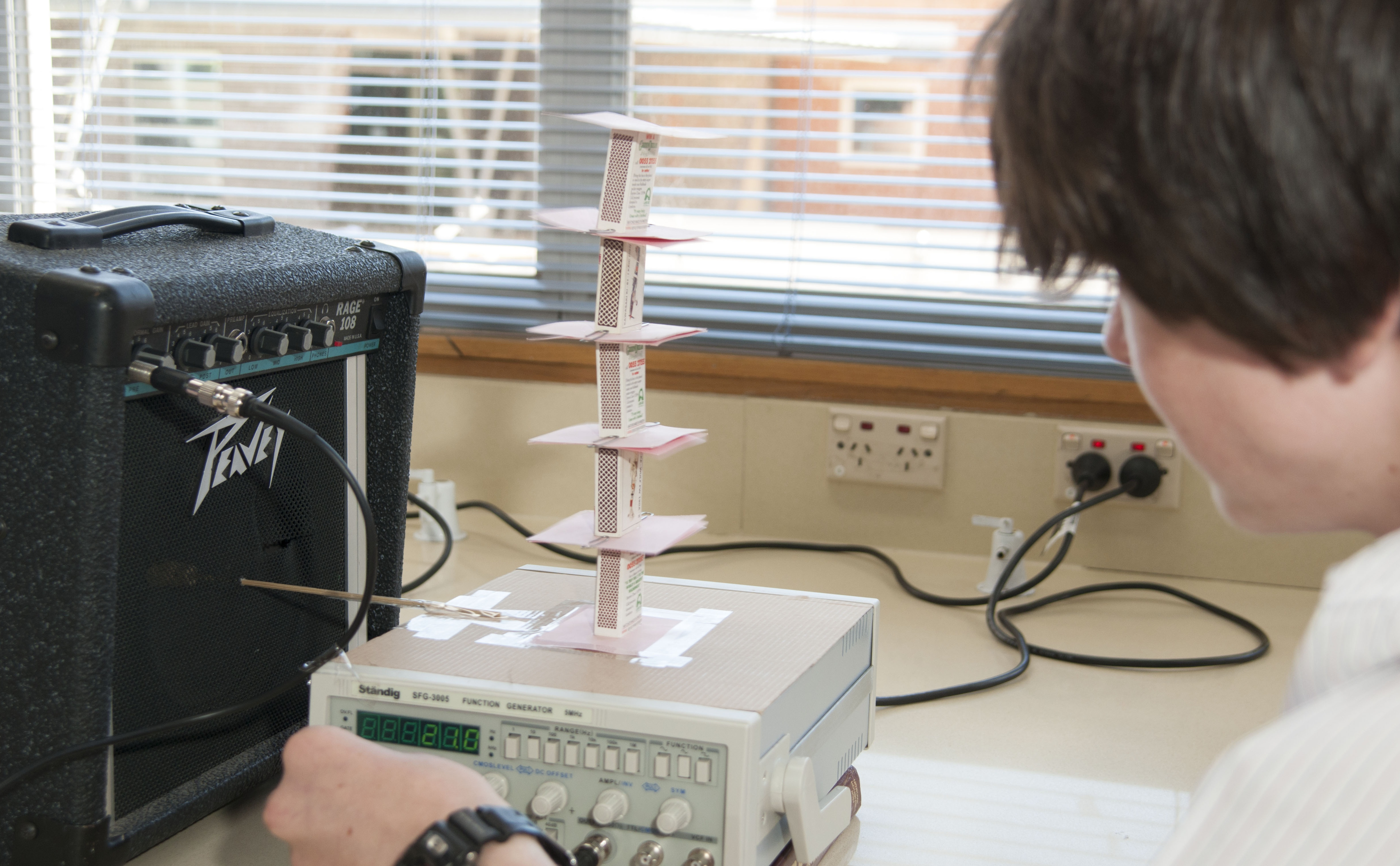 a student looks closely at his experiment