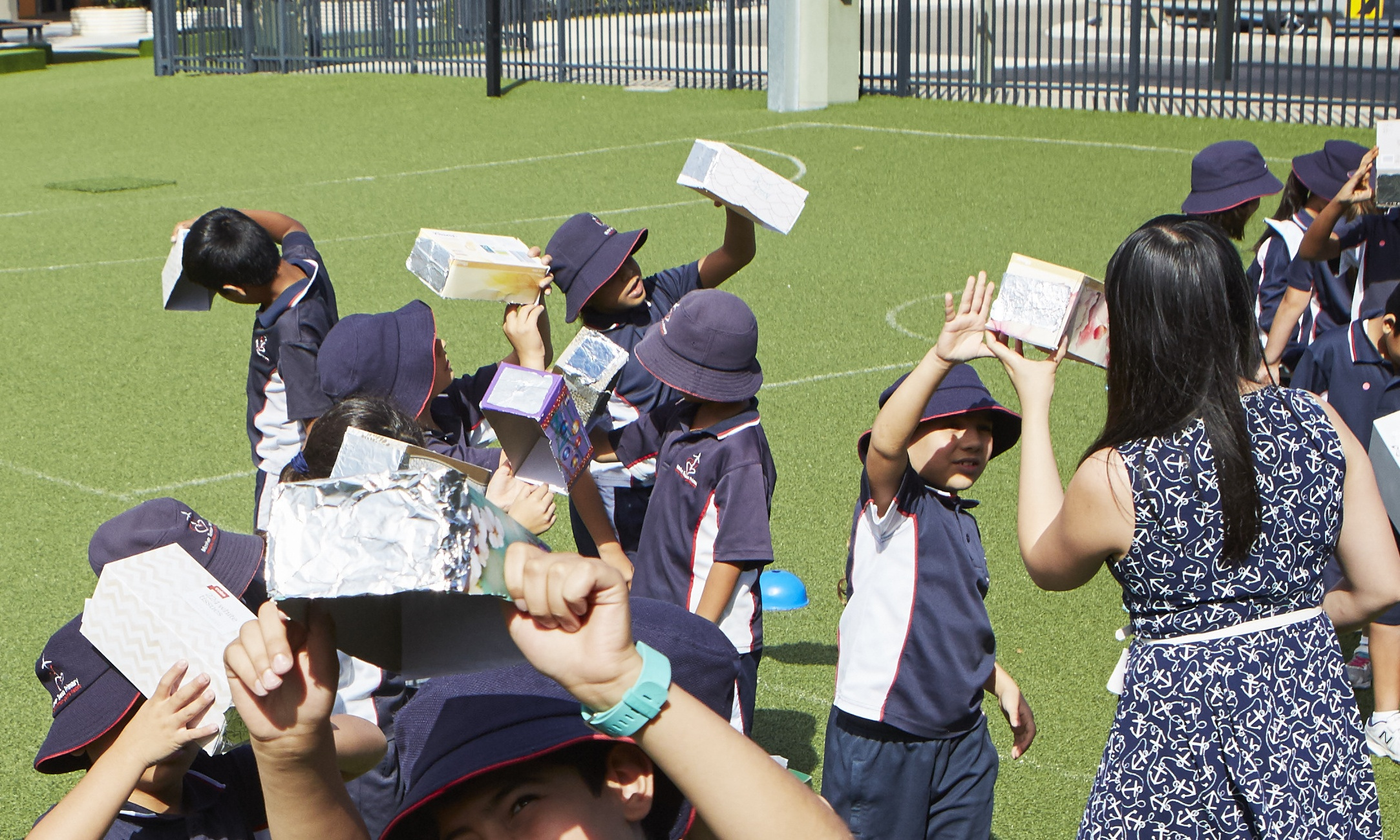 students testing their pin hole camera experiment in the field with their teacher
