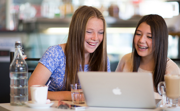 two girls sitting infront of a laptop computer discussing their work