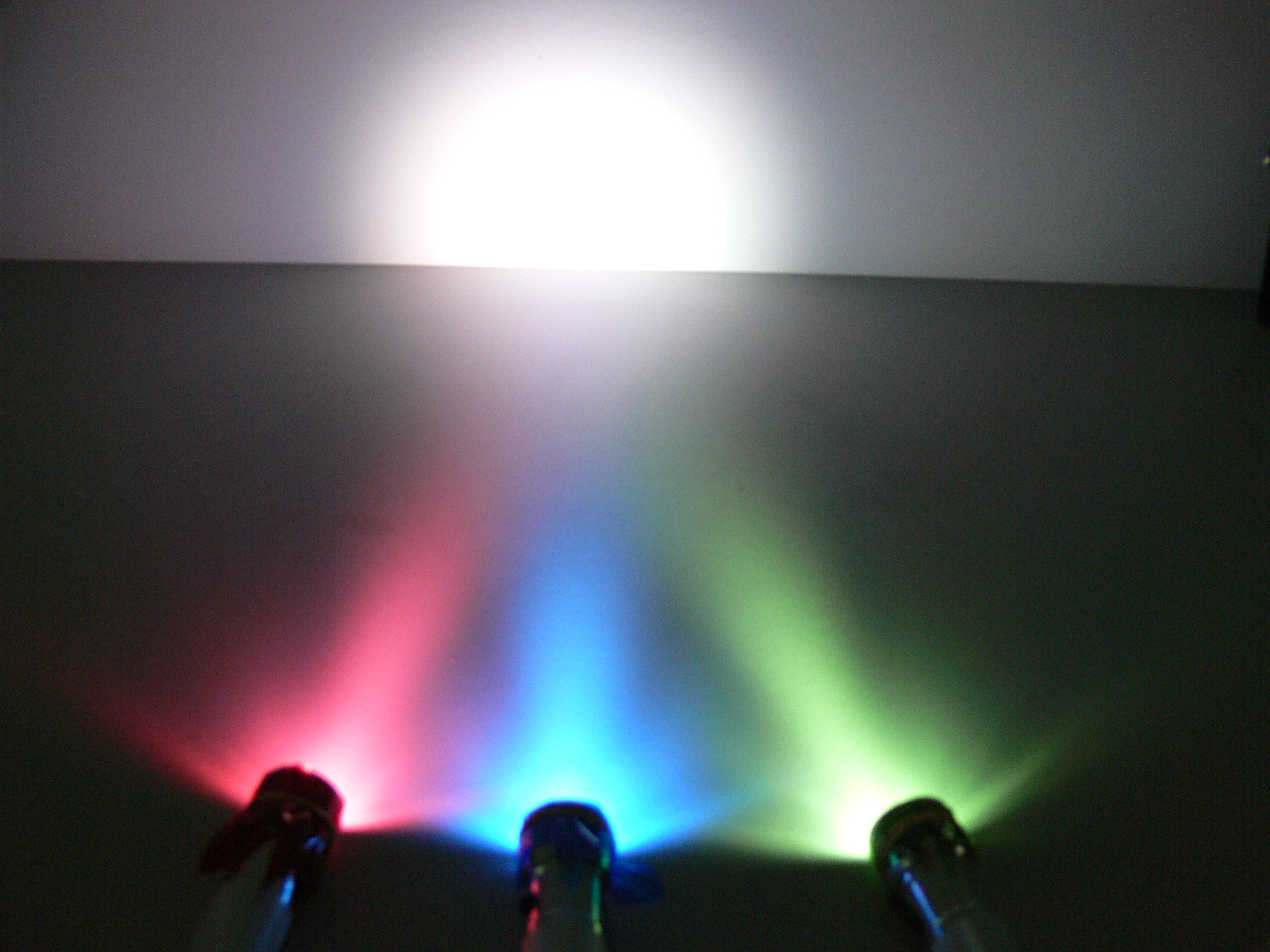 three torches covered with cellophane one red, one blue and one green all pointing into the same spot on the wall