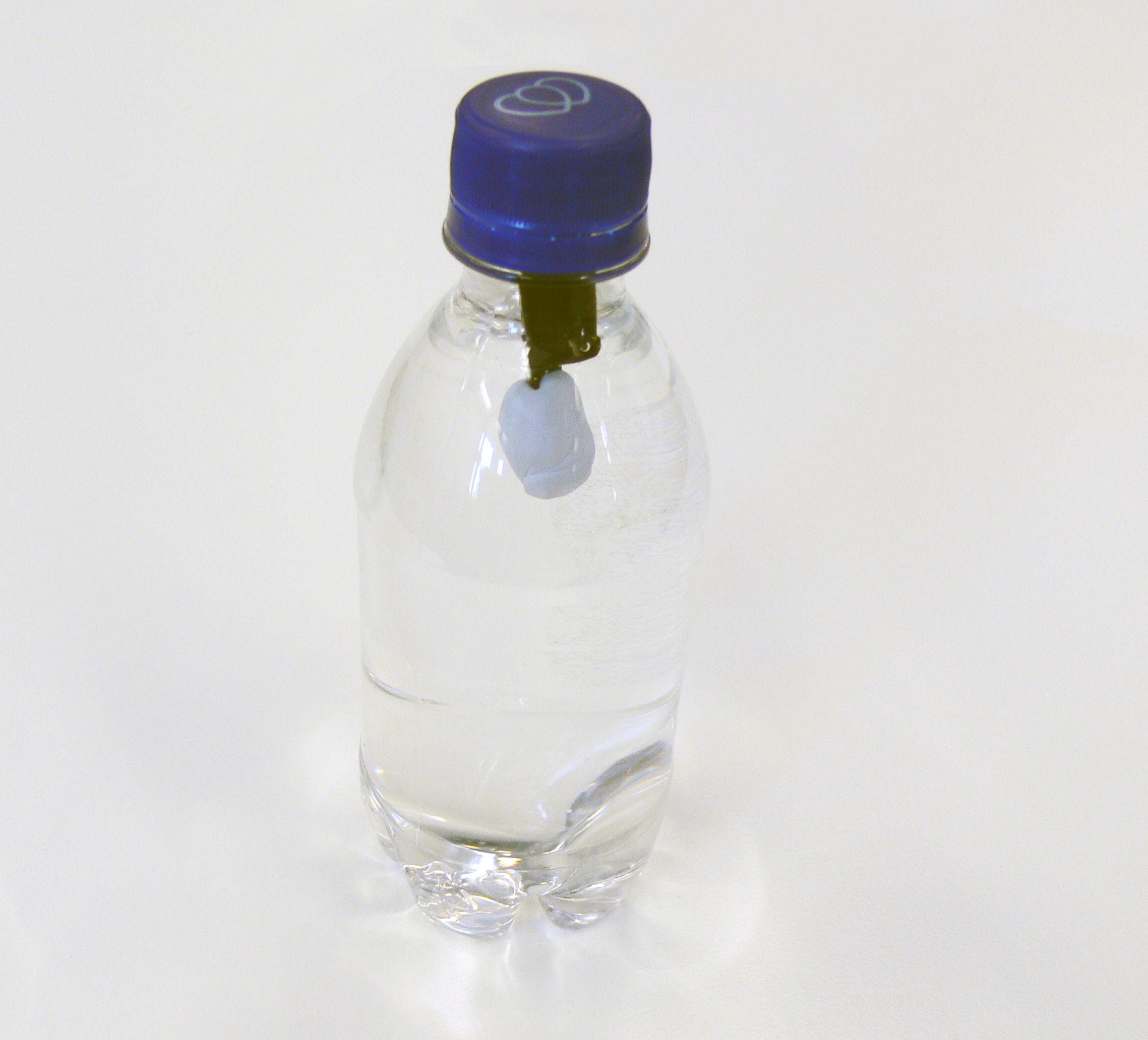 Bottle of water with floating pen lid  with blutack stuck to stem of pen lid
