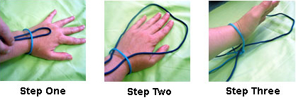 Hand with rope cuff tied around wrist with loop of joining rope to other cuff being pushed through hole between hand and rope
