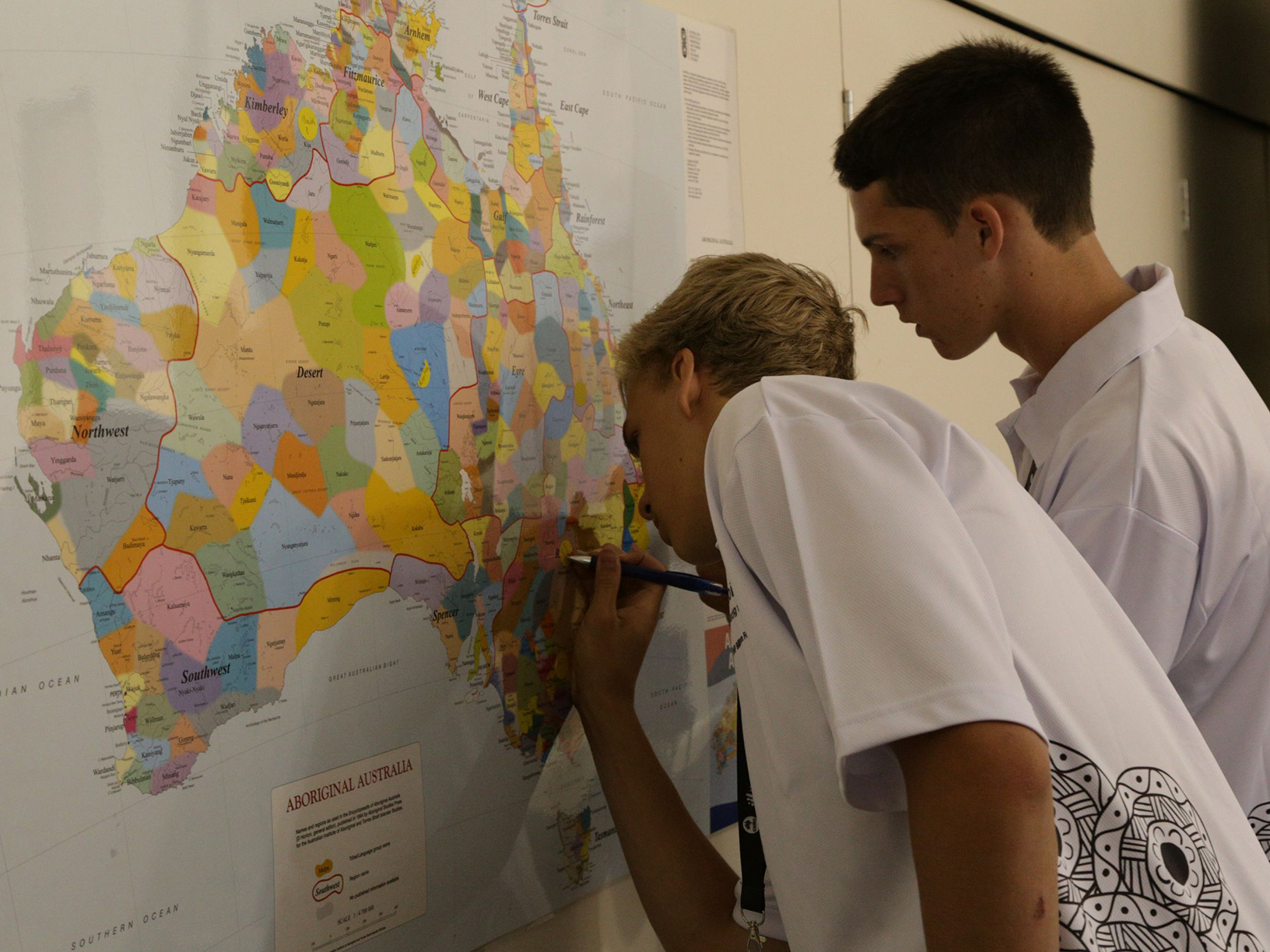 Two students mark on the map where they are from