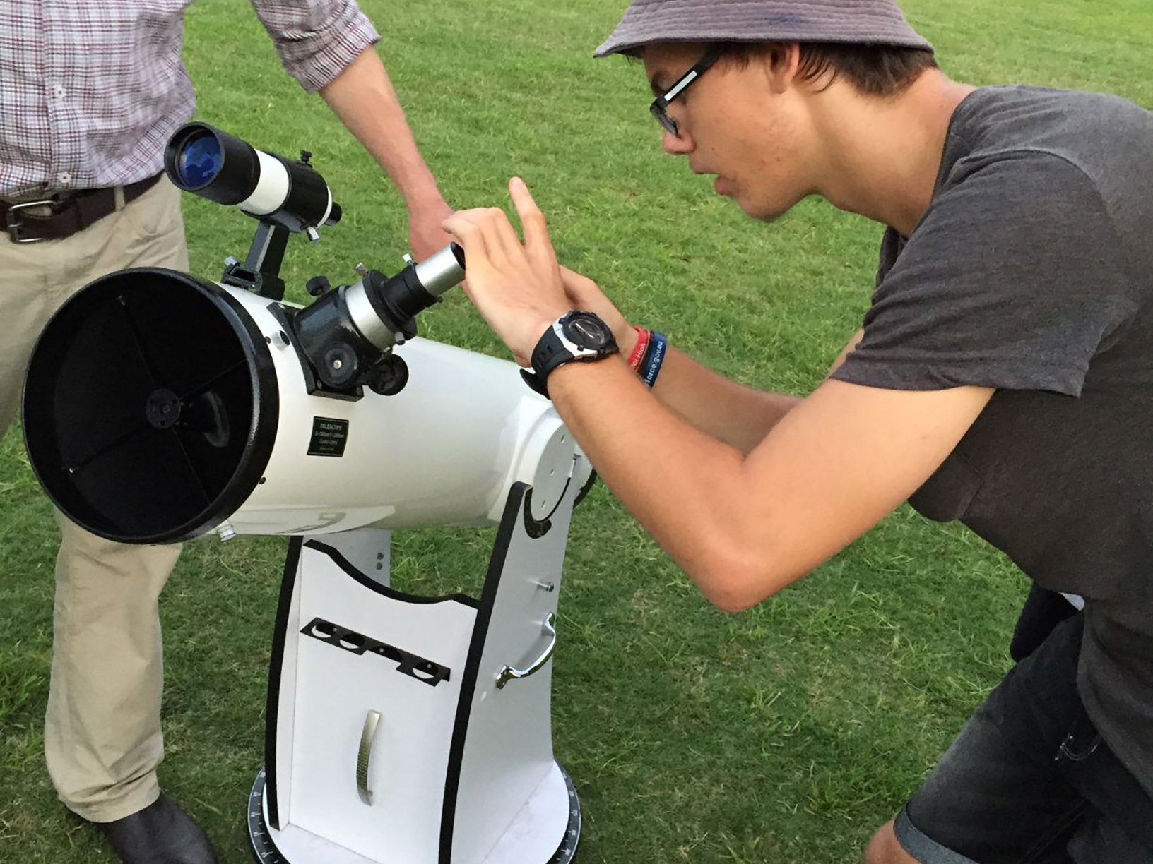 One student takes a photo through the eye piece of a telescope