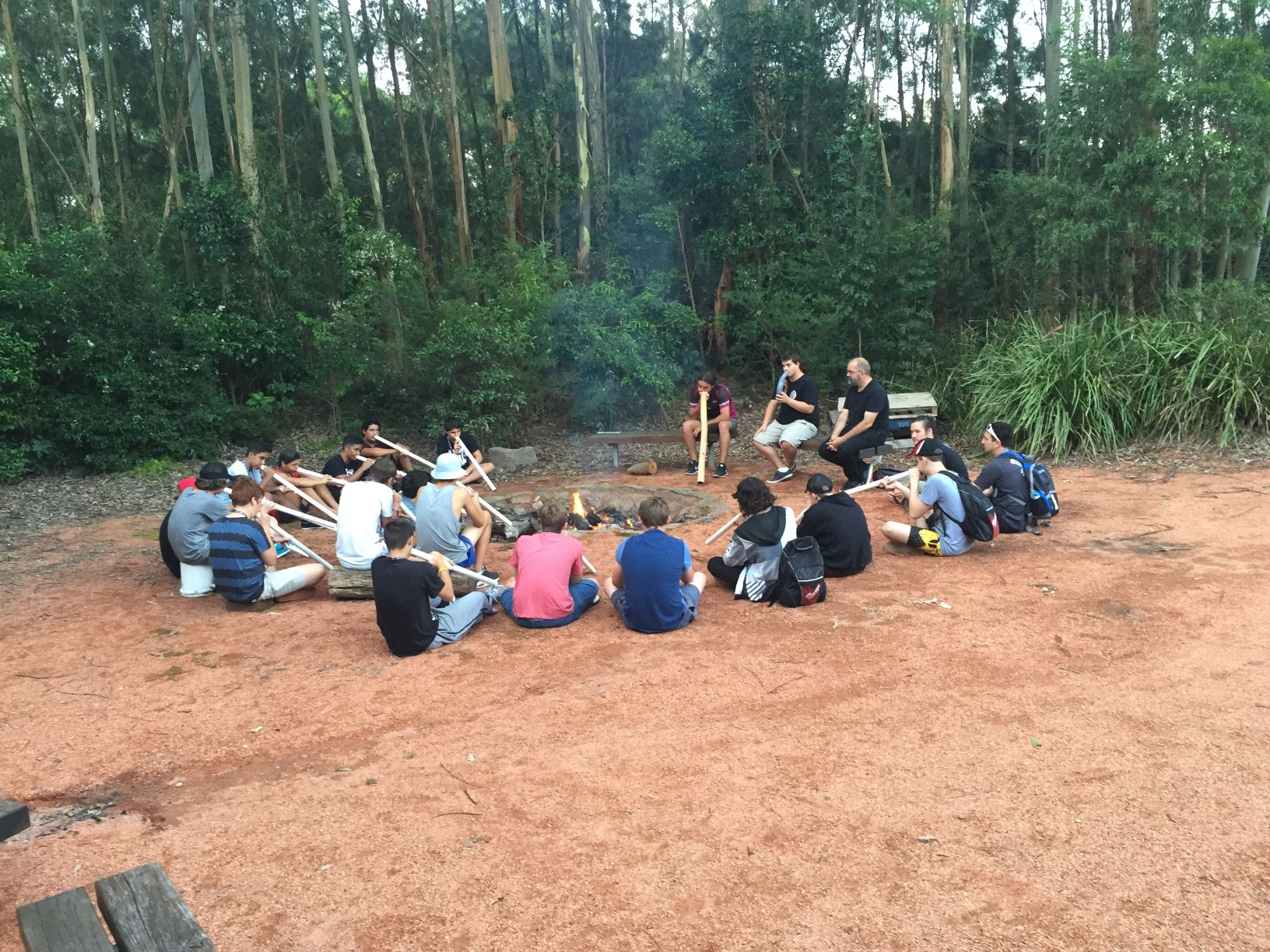 Fellas sit around the camp fire during digeridoo workshop